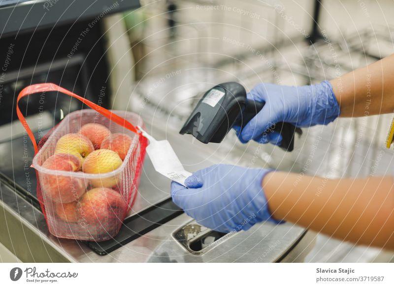 Scannen von Strichcode. Frau oder Arbeiter in blauen medizinischen Handschuhen, die einen Strichcode-Scanner halten und Papier auf Pfirsichfrüchten scannen. Einkaufen während der Coronavirus-Pandemie, selektiver Fokus