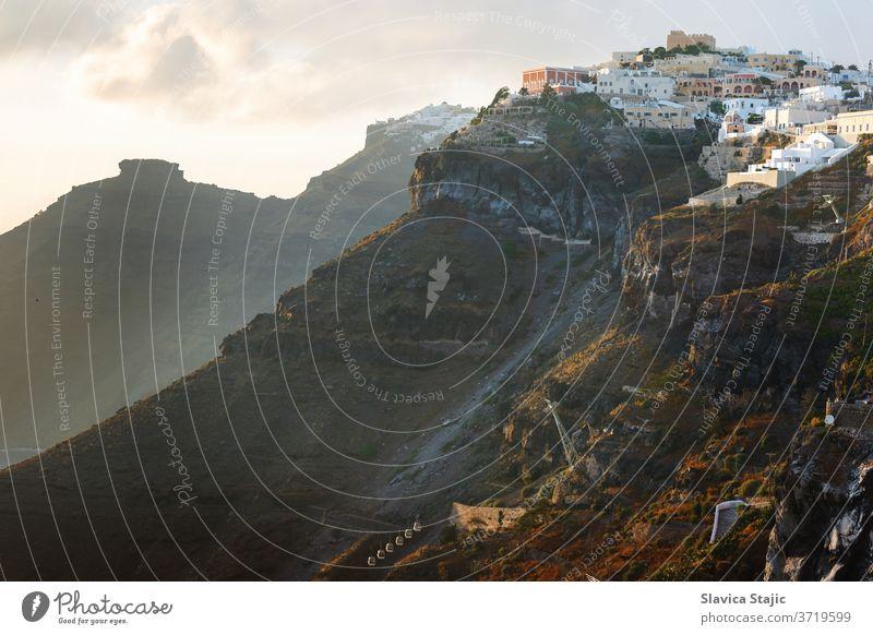 Sonnenuntergang auf der griechischen Insel Santorin mit farbenfrohem, warmem Licht und Wolken über der Stadt. Der Blick folgt dem Rand der Caldera von Thira, Skaros-Felsen und Imerovigli in Richtung Sonne