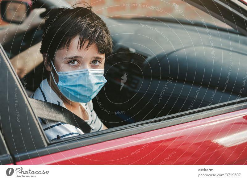 Kind mit medizinischer Maske, das in einem Auto fährt Coronavirus Virus medizinische Maske PKW KFZ Sicherheitsgurte Seuche Pandemie Quarantäne Familie covid-19