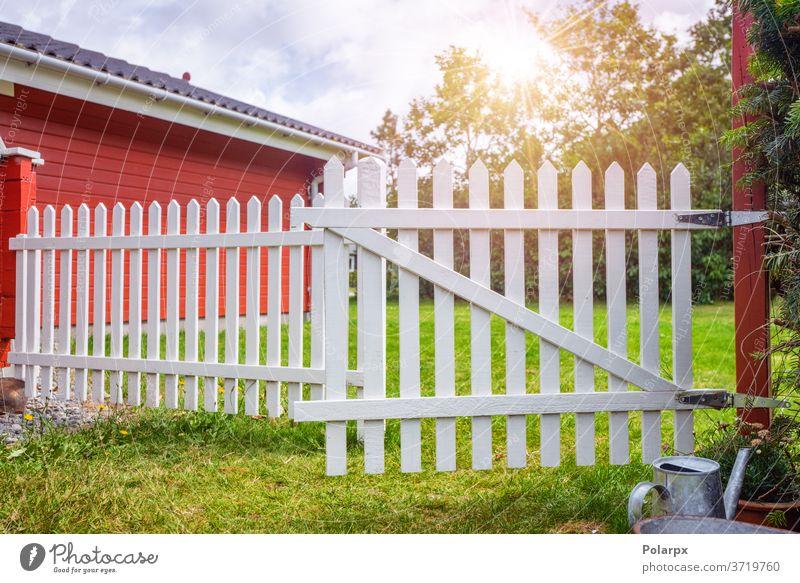 Weißer Lattenzaun in einem idyllischen Garten Schweden Landschaft Laubwerk Strauch Buchse Gras Leben friedlich Frühling Blütezeit Sonne Rasen Sommer Hinterhof