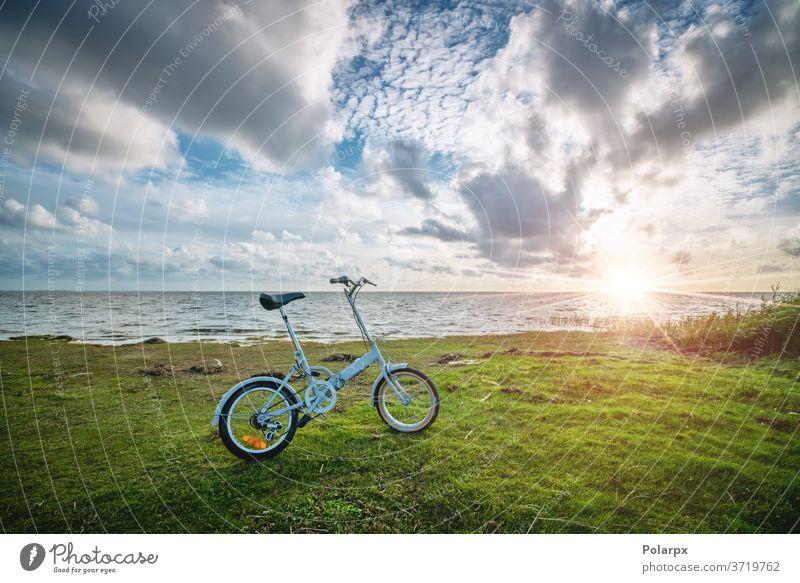 Faltbares Fahrrad am Meer bei Sonnenuntergang sonnig kompakt Sonnenaufgang hell durchstöbern Landschaft Sommer Pedal Fahrradfahren Radfahren im Freien Lifestyle