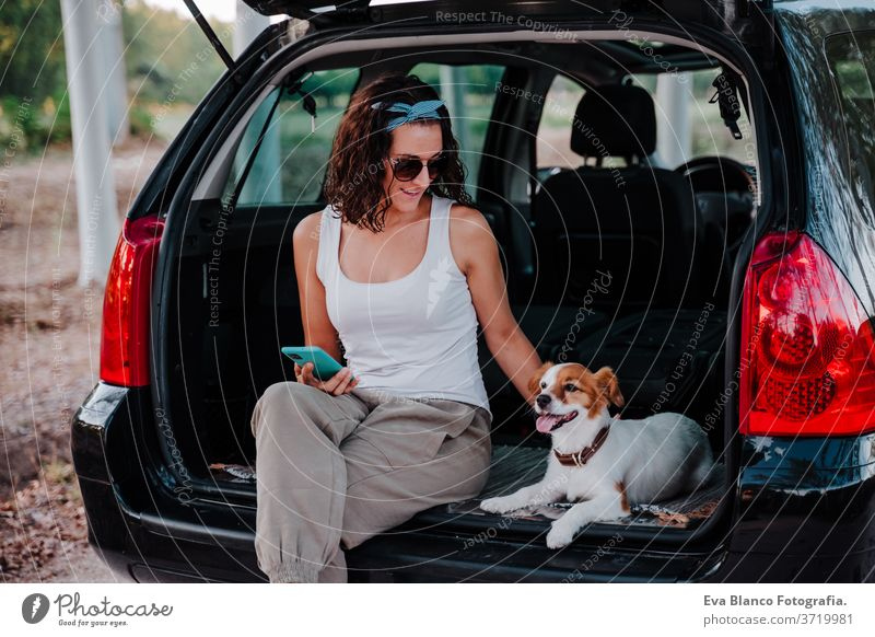 junge glückliche Frau in einem Auto, die sich mit ihrem süßen Hund vergnügt. Reisekonzept PKW reisen jack russell Zusammensein Liebe im Freien Lifestyle