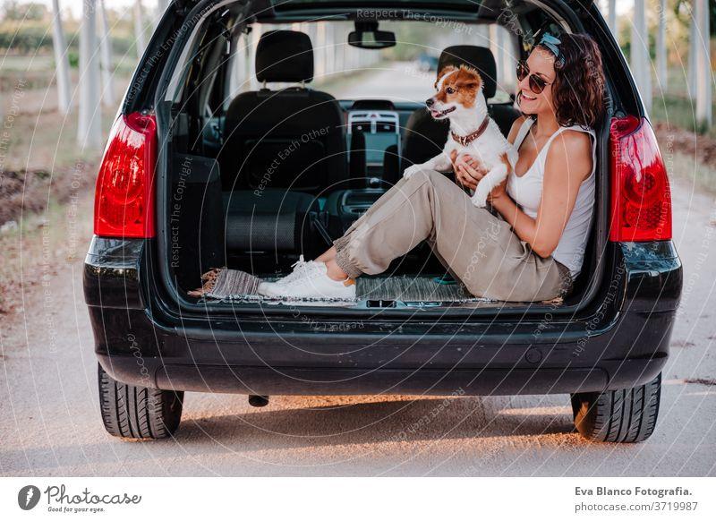 junge glückliche Frau in einem Auto, die ihren süßen Hund kuschelt. Reisekonzept PKW reisen jack russell Zusammensein Liebe im Freien Lifestyle Freundschaft