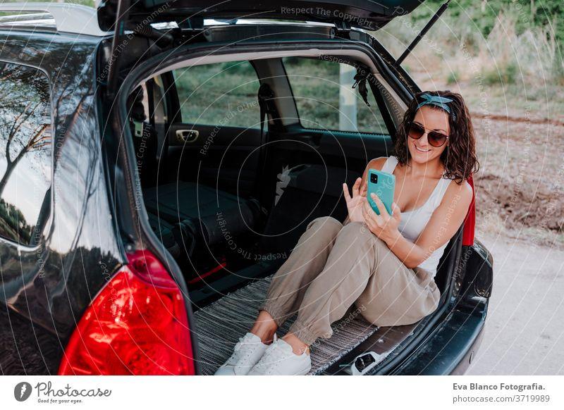 junge glückliche Frau in einem Auto, die ein Mobiltelefon benutzt. Reisekonzept PKW reisen Handy Glück Kaukasier Lächeln im Freien Warten Erwachsener