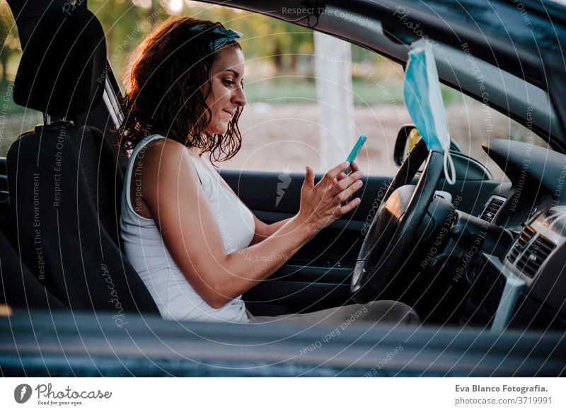 junge Frau in einem Auto. Schutzmaske, die am Rückspiegel hängt. Reisen und neues Normalkonzept PKW fahren Corona-Virus reisen Pollen Krankheit Prävention