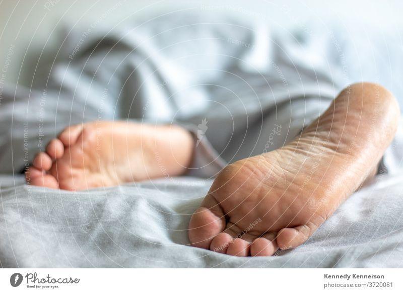 Frau/Mann im Bett, die sich unter einer Decke entspannen, wobei die Füße herausschauen Entspannung im Bett entspannend unter der Decke Schlafzimmer Fuß