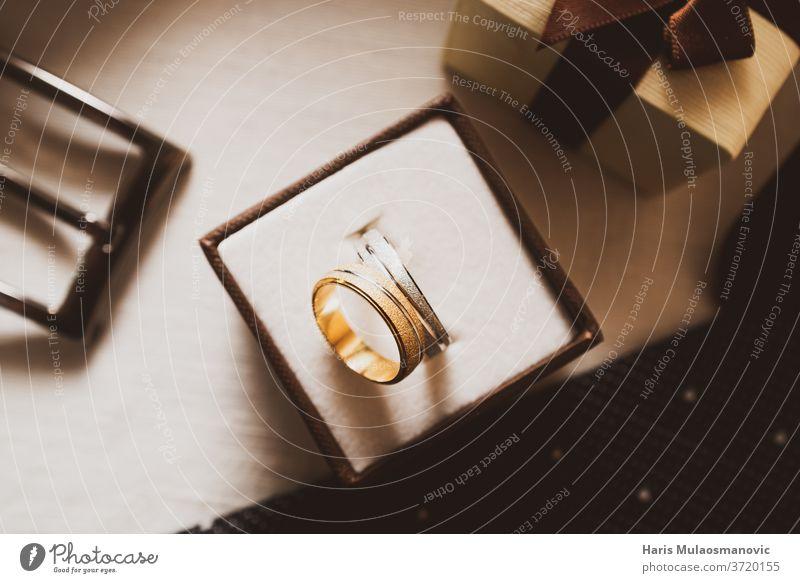 Trauringe in der Schachtel und Armbanduhr Hintergrund schön Schönheit Gurt schwarz Kasten braun Business Nahaufnahme Konzept Paar Design Eleganz Engagement Mode