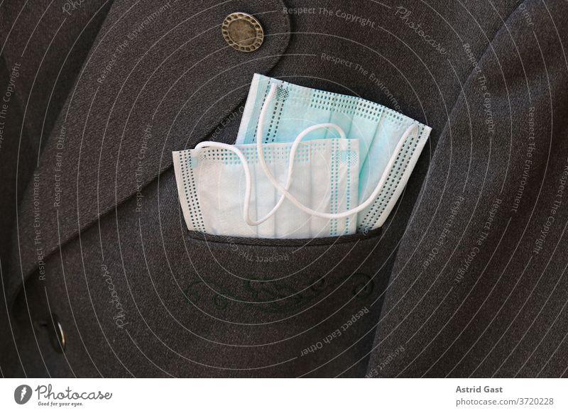 In einem Anzug stecken zwei Corona-Mundschutzmasken. Schutzmasken im Alltag und Geschäftswelt maskenpflicht op-masken mundschutzmasken anzug kleidung alltag