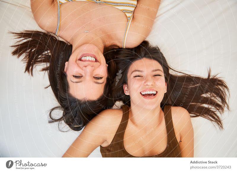 Lächelnde Frauen, die zusammen auf dem Bett ruhen Freundschaft bester Freund Zusammensein Lügen Wochenende genießen heiter weich freundlich heimwärts