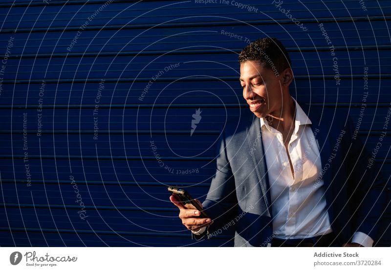 Fröhlicher Geschäftsmann im formalen Anzug surft auf dem Smartphone benutzend Glück Erfolg Nachricht heiter Telefon lesen jung Mann Afroamerikaner ethnisch
