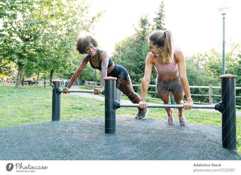 Sportliche Frauen machen Liegestütze im Park Fitness Training hochschieben heiter Zusammensein Übung sportlich Freund jung rassenübergreifend multiethnisch