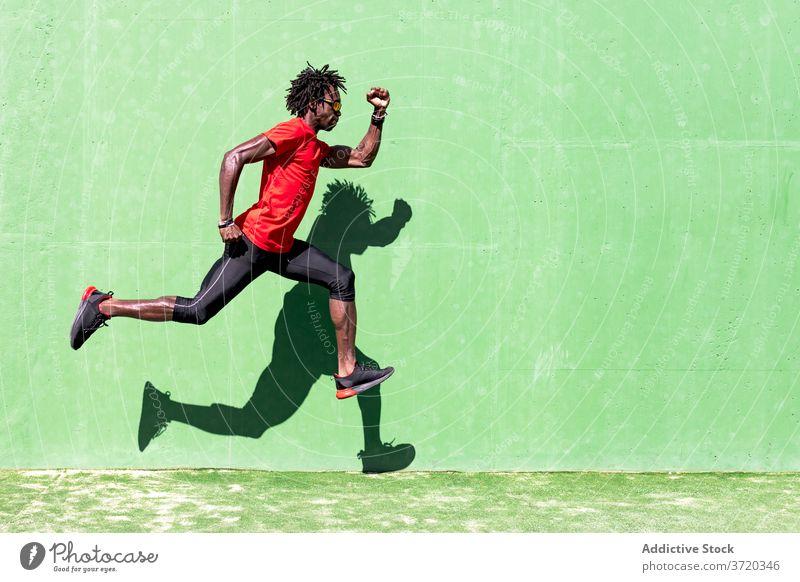 Fitter männlicher Sportler beim Training auf dem Sportplatz springen Mann Sommer intensiv passen Moment Übung ethnisch schwarz Afroamerikaner Sportkleidung