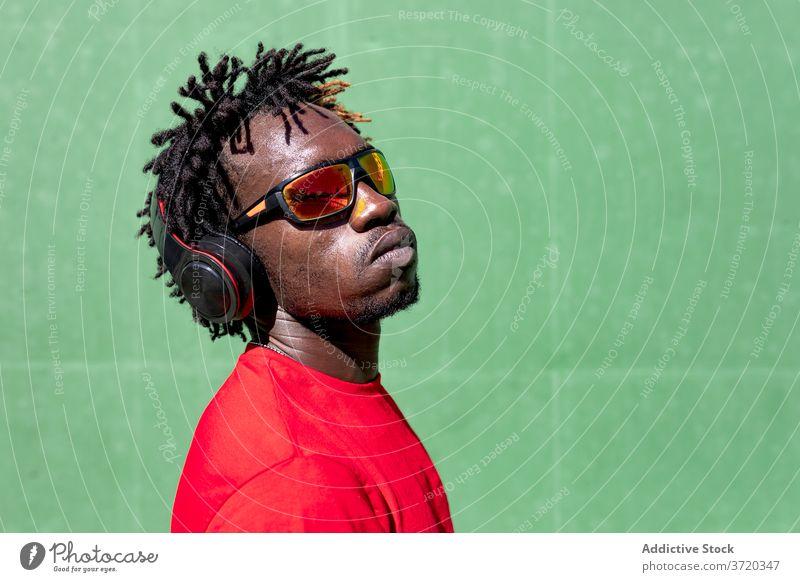Schwarzer Sportler beim Musikhören zuhören Kopfhörer Mann Rastalocken Athlet vorbereiten Training genießen männlich ethnisch schwarz Afroamerikaner Gesundheit
