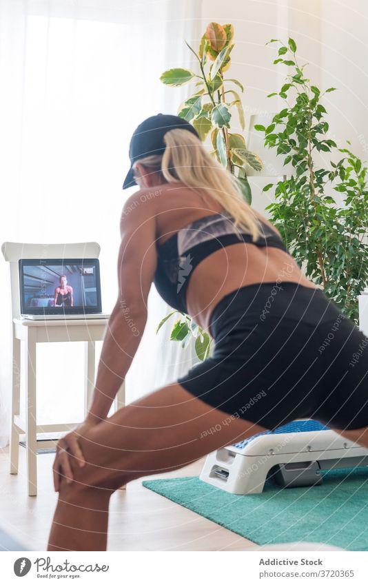 Schlanke Frau macht Übungen zu Hause Seitenlonge heimwärts Training online Video Tutorial zuschauen benutzend Laptop Fitness Apparatur Gerät Internet Sport
