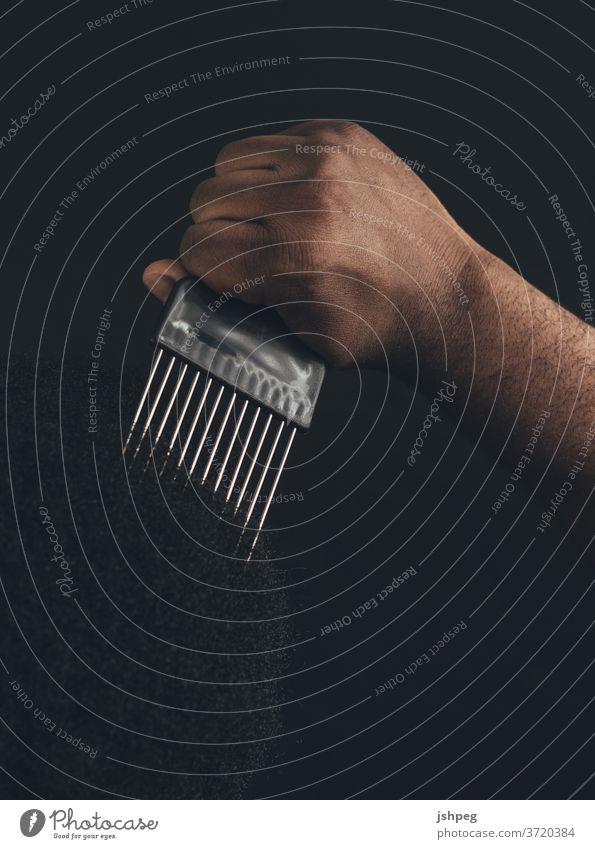 Schwarzer Mann mit Kamm pflücken Pickelkamm schwarz BLM Schwarze Leben Materie Kamm verwenden Haarpflege Haare & Frisuren Behaarung Schwarzes Haar Haarkleid