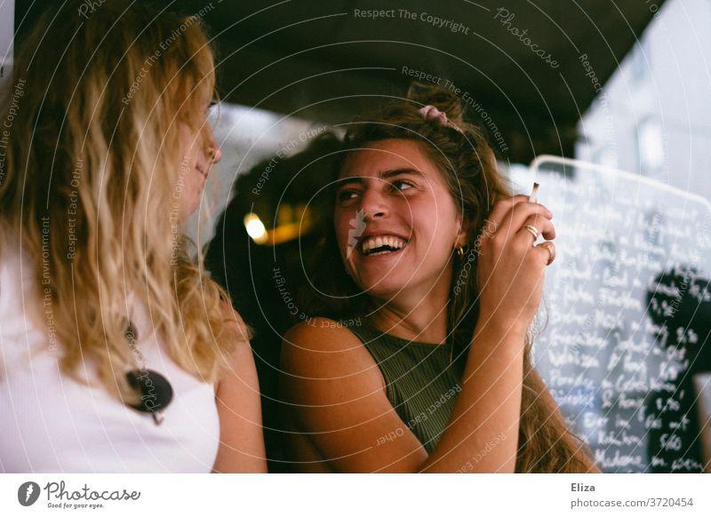 Zwei Freundinnen sitzen draußen im Café und lachen zusammen Bar rauchen Spaß haben Sommer Fröhlichkeit zwei unterhalten ausgehen Lifestyle Freundschaft