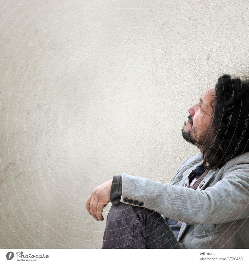 Die Suche nach dem Sinn des Lebens. Oder vielleicht der Versuch, alle Sinne zu beleben? Mann sitzen lässig cool zweifeln nachdenken attraktiv ernst Bart Locken