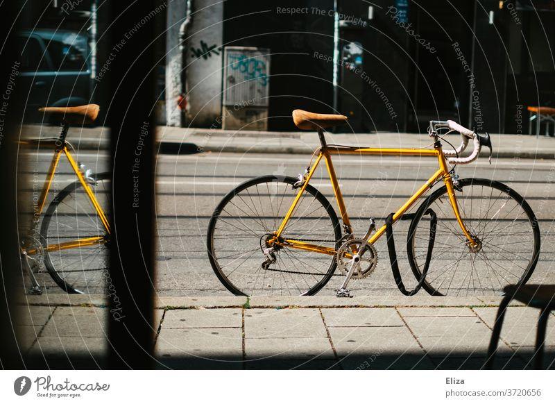 Gelbes vintage Rennrad steht abgeschlossen auf der Straße vor einem Geschäft Fahrradschloss gelb Fahrradfahren retro Sattel Ledersattel Sport Lifestyle trendy