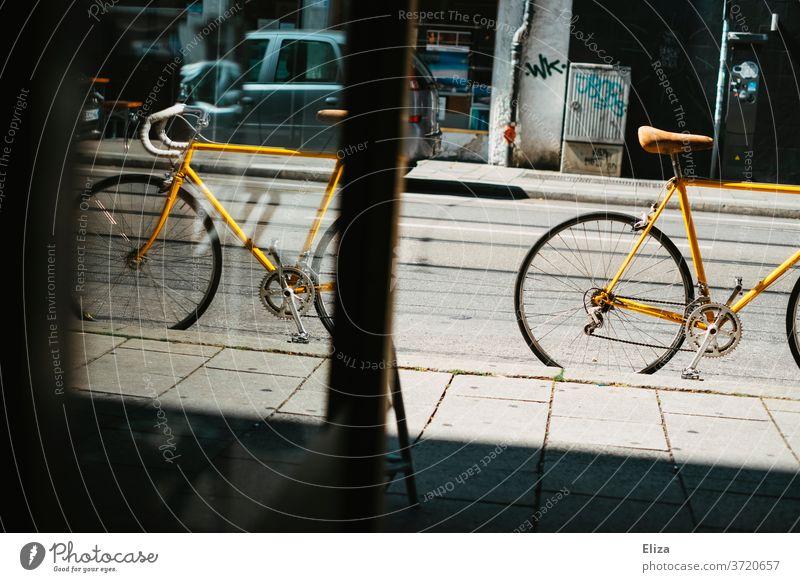 Gelbes vintage Rennrad steht auf der Straße vor einem Geschäft gelb Fahrrad Fahrradfahren retro Sattel Ledersattel Sport Lifestyle trendy Mobilität hip Schloss