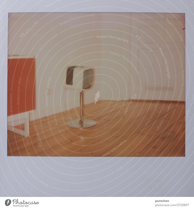 In einer Altbauwohnung steht ein Fernseher auf einem Standbein und ein Sideboard. Vintage, 60s. Vergangenes. dielen fernseher standbein vintage 60er 70er