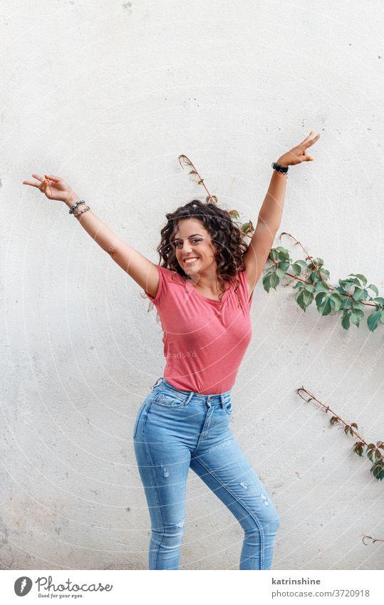Junge Frauen mit erhobenen Händen bleiben in der Nähe einer Wand jung Mädchen anhaben nach oben Attrappe T-Shirt Jeanshose Aufenthalt Lächeln Rundhals