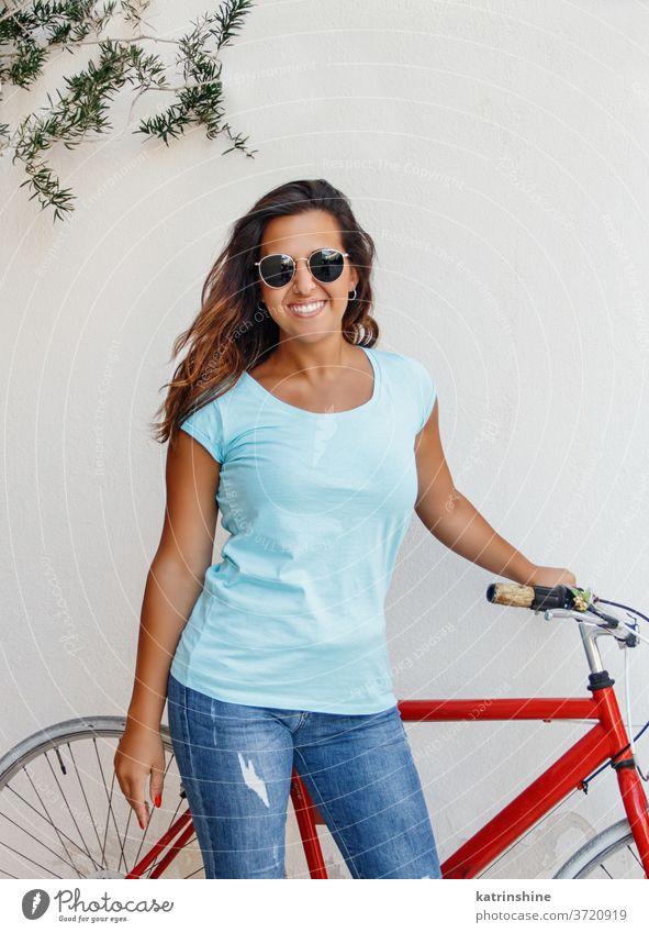 Junge Frauen mit Fahrrad halten sich in der Nähe einer Mauer auf jung Mädchen anhaben Attrappe T-Shirt Jeanshose Aufenthalt Wand Lächeln Rundhals
