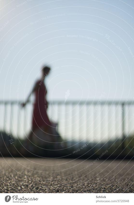 Junge Frau geht mit Tasche vor einem Geländer über Asphalt starke Unschärfe gehen Profil unscharf Himmel blau Kleid Sommer Gegenlicht Silhouette
