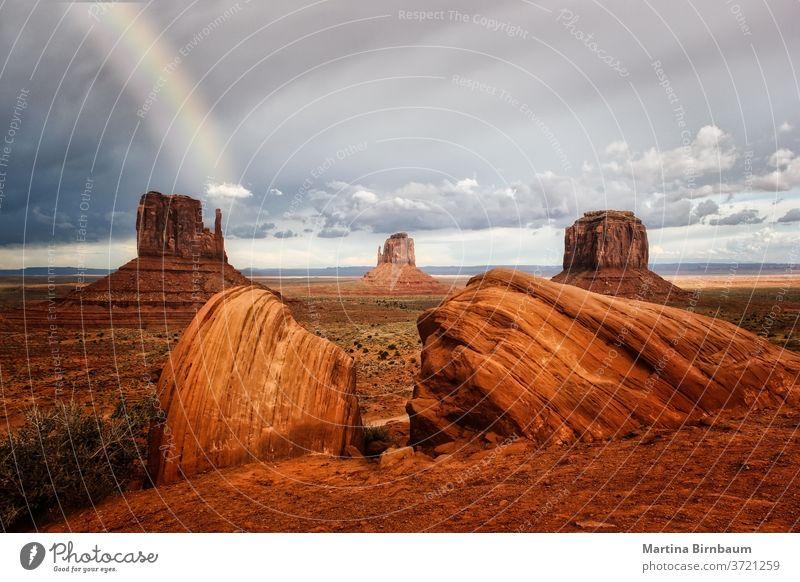 Dunkle Wolken und ein Regenbogen über dem Monument Valley, Arizona Tal Denkmal USA Landschaft wüst Unwetter Park navajo Felsen rot Sandstein Natur schön