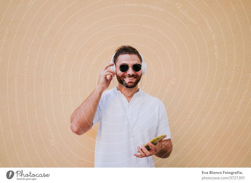 glücklicher junger Mann im Freien, der mit Handy und Headset Musik hört. Technologie und Lebensstil hören Technik & Technologie Großstadt urban Glück Lächeln