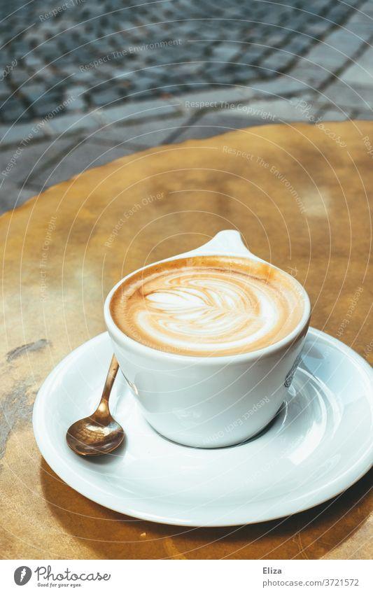 Eine Tasse Cappuccino auf einem goldenen Tisch im Café Kaffee Latte Art Koffein Getränk Kaffeetrinken Kaffeepause lecker warm Kaffeetasse Heißgetränk Löffel