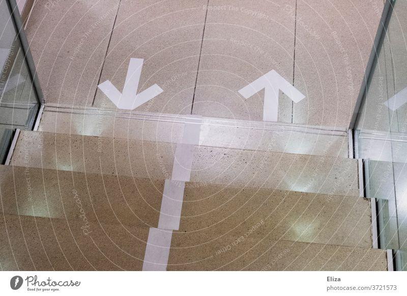 Richtungsweisende Pfeile auf dem Boden vor einer Treppe. Vorgabe der Laufrichtung in Corona Zeiten. Corona Maßnahmen drinnen richtungsweisend wegweisend