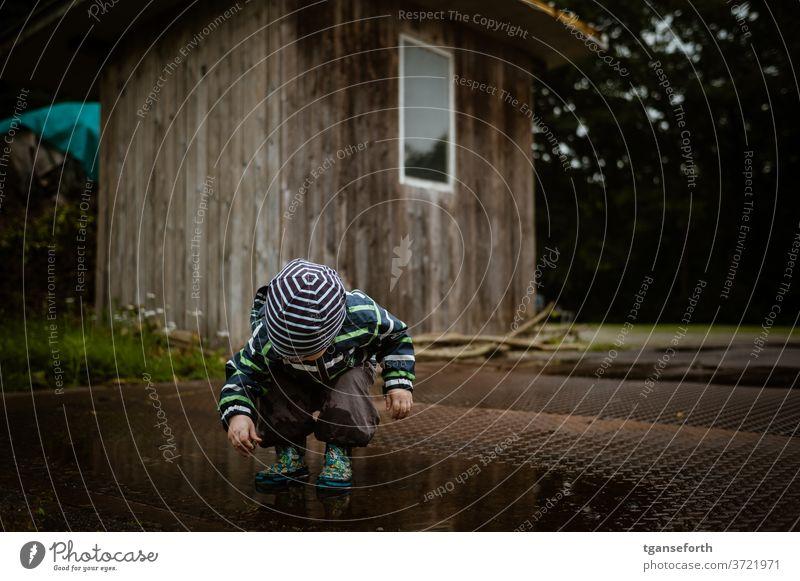 Junge spielt in Pfütze Kind Kindheit Spielen spielende Kinder Außenaufnahme Freude Menschen entdecken beobachten 1-3 Jahre Kindererziehung Kleinkind