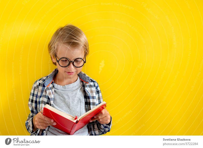 Porträt eines niedlichen und klugen blonden kaukasischen Jungen in einem karierten Hemd auf gelbem Hintergrund. 1. September-Tag. Bildung und zurück zum Schulkonzept. Kinderschüler bereit zu lernen und zu studieren.