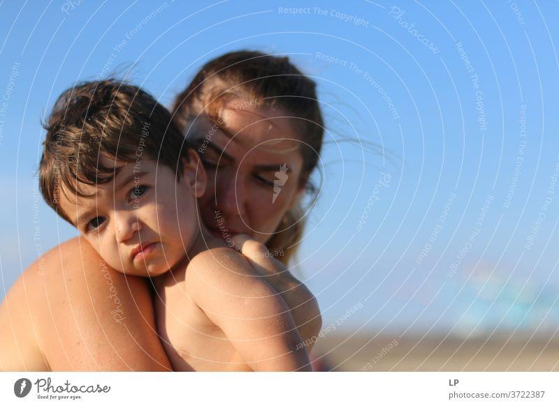 Mutter, die ein Kind im Arm hält Badeurlaub Strand Freude Warmherzigkeit Gelassenheit Windstille Sonnenlicht Traurigkeit Zeit Sehnsucht Ausdauer Kontakt Sommer