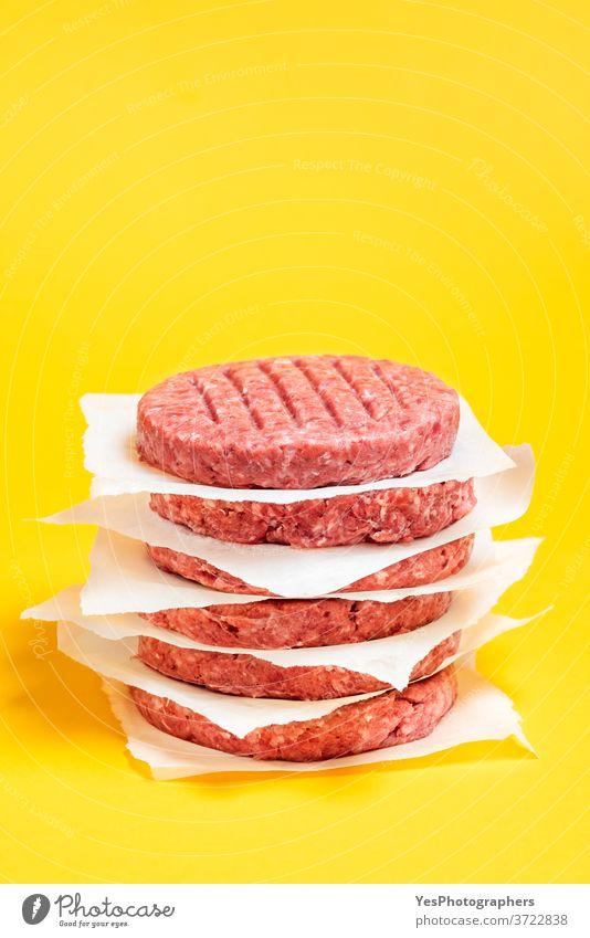 Burger-Pasteten auf dem Tisch gestapelt. Rohe Rinderfrikadellen isoliert auf gelbem Hintergrund. Barbecue grillen Rindfleisch Metzger Nahaufnahme Komfortnahrung
