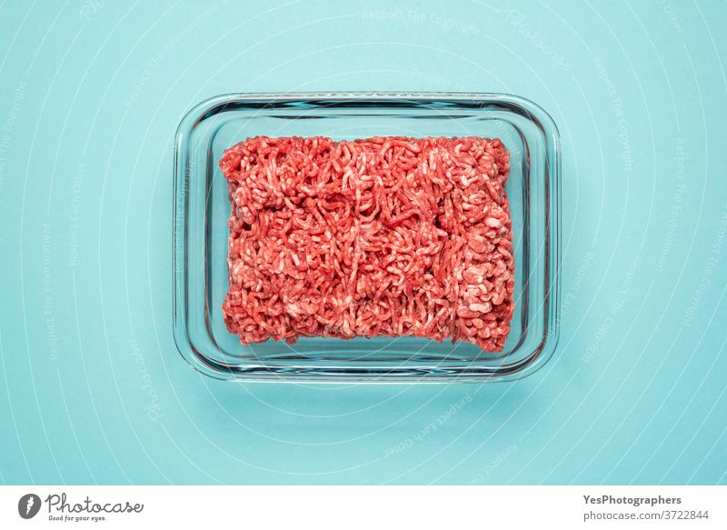 Rohes Rindfleisch in einem Lebensmittelbehälter aus Glas. Gemahlenes Fleisch in Glasschale, isoliert auf farbigem Hintergrund obere Ansicht blau
