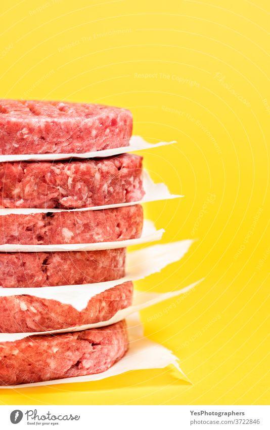 Nahaufnahme von rohen Rinderpasteten. Burgerfrikadellen vor gelbem Hintergrund gestapelt. Barbecue grillen Rindfleisch Metzger Komfortnahrung Essen zubereiten