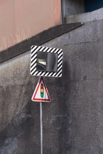 Verkehrsspiegel und Verkehrszeichen Ampel vor Betonwand einer Unterführung Spiegel Konvexspiegel Auto Spiegelung winzig Gräser Streiflicht Straßenverkehr