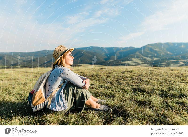Junge weibliche Naturliebhaberin genießt den Sonnenuntergang in den Bergen Abenteuer allein Rucksack Backpacker Tasche schön lässig Fundstück genießend Umwelt