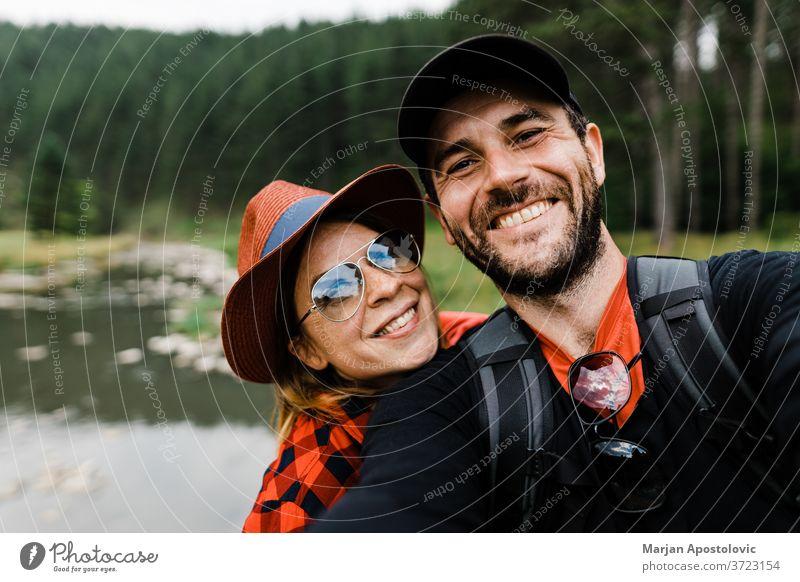 Selfie eines jungen Paares in den Bergen am Fluss 30s aktiv Erwachsener Abenteuer Rucksack Rucksacktouristen Rucksacktourismus Freund Fotokamera lässig