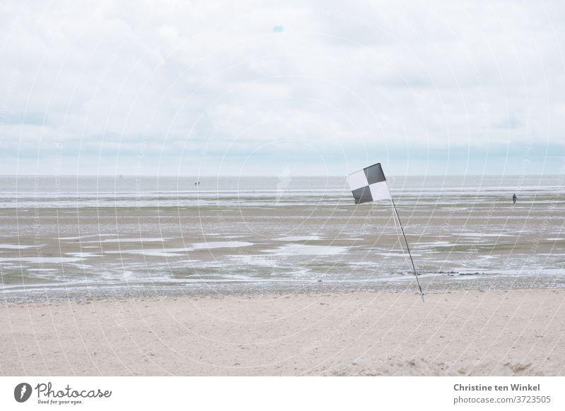 Blick auf die Nordsee und das Watt bei Niedrigwasser an einem trüben windigen Tag. Drei Wattwanderer sind unterwegs. Am Strand steht im Vordergrund eine schwarz-weisse Flagge.