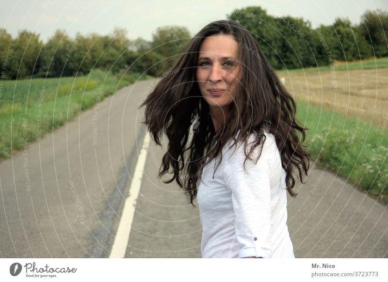 Frau mit langen wehenden Haaren schaut in die Kamera Haare & Frisuren Bewegung Straße Wege & Pfade feminin Lächeln schwungvoll Schwung Gute Laune spontan