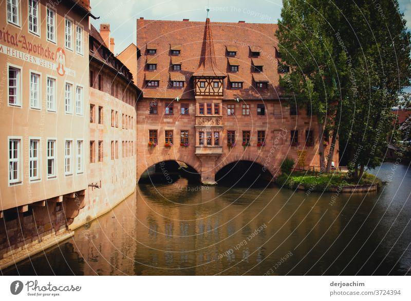 Spital Apotheke  Nürnberg , Architektur im alten Stil . Ein Fluß durchfließt das Gebäude. Da neben steht ein Baum. Franken Außenaufnahme Farbfoto historisch