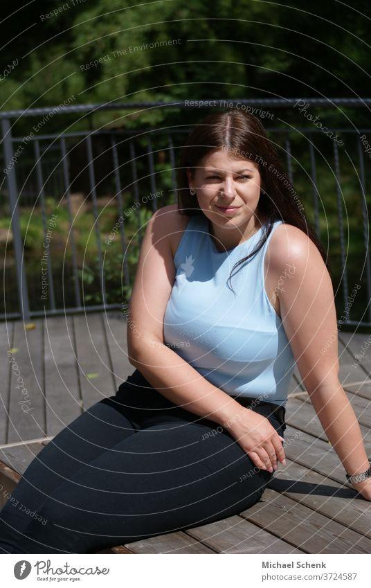 Junge Frau mit offenen Haar sitzt auf einer Holzterrasse in der Sonne Frau,sonne, Porträt Tag Außenaufnahme Farbfoto Zufriedenheit Gelassenheit natürlich