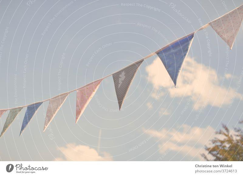 selbstgenähte Wimpelkette aus bunten Stoffen im Sonnenlicht vor leicht bewölktem blauen Himmel selbstgemacht Stoffmuster Wolken romantisch mehrfarbig