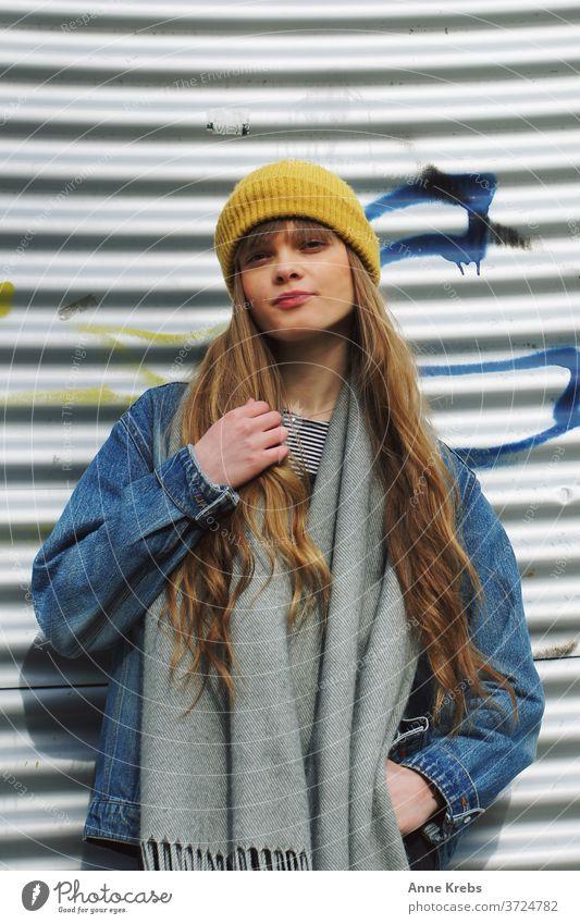 Portrait einer jungen Frau Mädchen Street lange Haare Mütze gelb blau blond Cool schön attraktiv Model hübsch Mensch streetstyle Streetlife Jeansjacke frontal