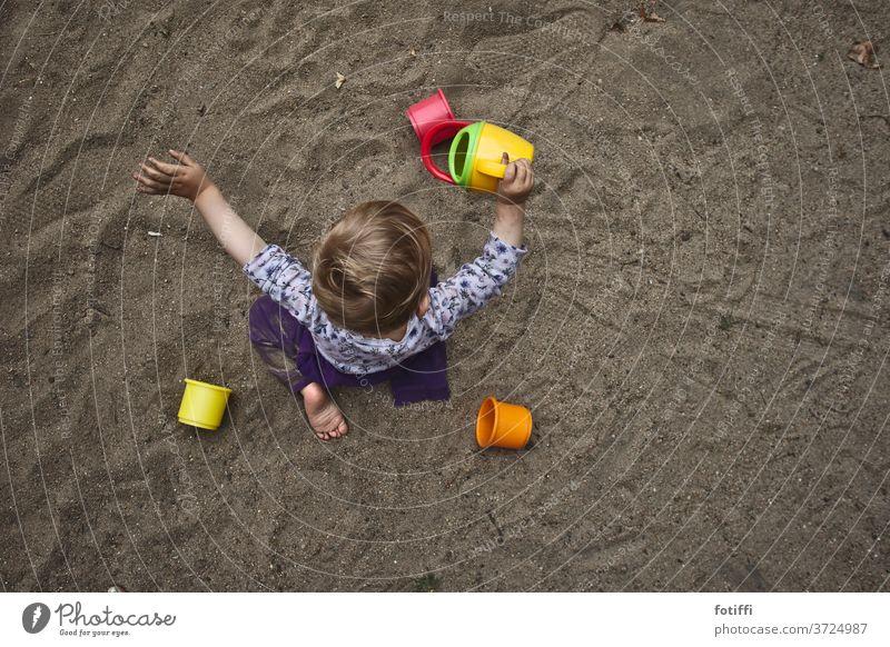 Sandkind Sandspielzeug Kind Vogelperspektive Spielen Spielzeug Sandkasten versunken Kindheit rieseln Außenaufnahme Spielplatz Kinderspiel Kleinkind Tag