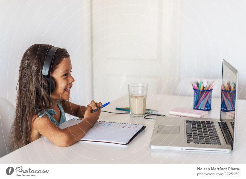 Kleines hispanisches Mädchen, das vor dem Laptop lernt. E-learning, zu Hause online lernen. Computer Kinder jung Video Schule Bildung E-Learning Lernen