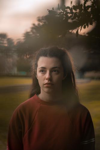 Die Aufmerksamkeit einer jungen Frau wird von etwas erregt, das wir nicht sehen können, wenn sie zwischen den Bäumen steht. rot Sonnenuntergang glühen Wärme