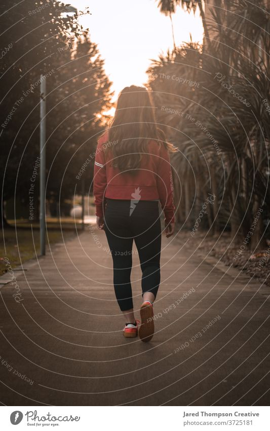 Eine junge Frau begibt sich auf einen von Bäumen gesäumten Weg, gebadet von der warmen Glut des Sonnenuntergangs. rot glühen Wärme lange Haare Mädchen Teenager